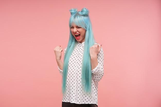 Muito jovem e animada de cabelos azuis levantando alegremente os punhos e gritando de alegria, regozijando-se com algo bom que aconteceu, de pé