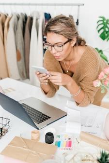 Muito jovem e casual assistente de loja em uma boutique moderna, curvando-se sobre a mesa enquanto rola a tela no smartphone no trabalho
