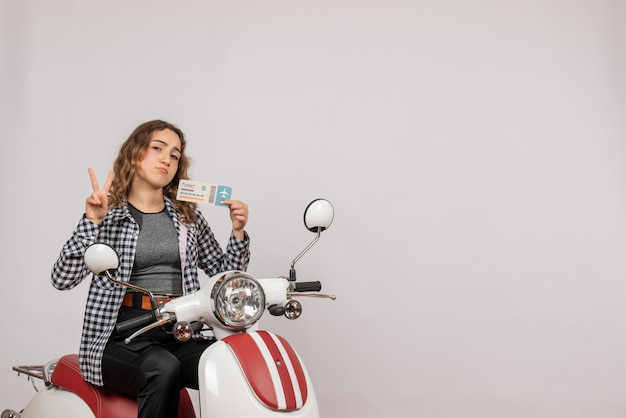 Muito jovem em ciclomotor segurando bilhete fazendo sinal ok em cinza