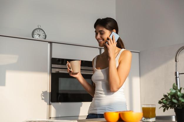Muito jovem em pé na cozinha de manhã, tomando uma xícara de café, falando no celular