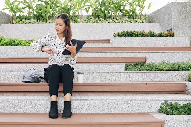 Muito jovem empresária sentada ao ar livre com um computador tablet nas mãos e verificando as horas de serviço enquanto espera por um colega