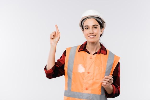 Muito jovem engenheira de capacete e jaqueta laranja apontando para cima, isolada, enquanto olha para você