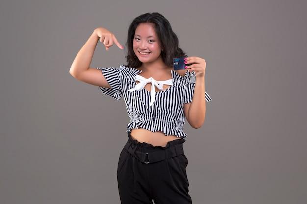 Muito jovem, feliz e sorridente, chinesa mostrando cartão de crédito