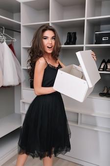 Muito jovem, felizmente surpresa garota em um belo guarda-roupa com caixa de sapatos novos, comprou calçados novos. ela tem cabelos castanhos compridos e cacheados, usando um vestido preto glamoroso.