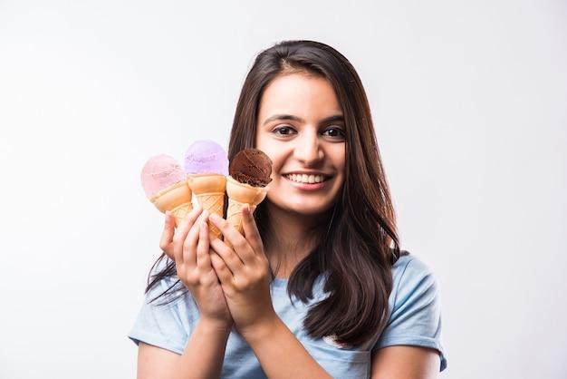 Muito jovem garota indiana asiática comendo ou apresentando sorvete em cones, isolada sobre um fundo branco