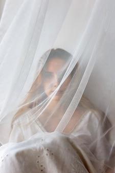 Muito jovem garota sensual vestido branco se escondendo atrás da cortina. conceito de beleza escondido
