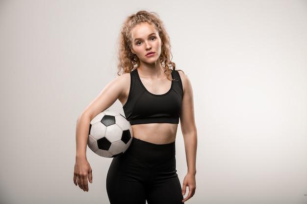 Muito jovem jogadora de futebol com longos cabelos loiros cacheados segurando uma bola entre o braço e a cintura
