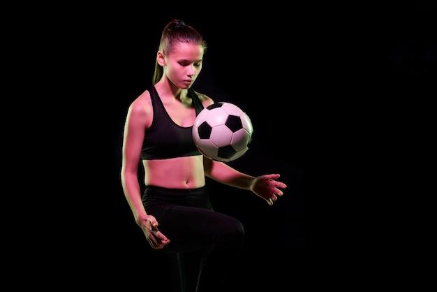 Muito jovem jogadora de futebol feminino em sportswear treinando com uma bola de futebol isolada na frente da câmera sobre um fundo preto