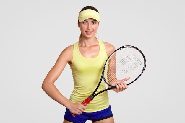 Muito jovem jogadora de tênis, detém raquete, pronta para acertar o vencedor e deixar a bola saltar, veste camiseta amarela, boné e bermuda azul, tem uma pele saudável e pura, entra para o esporte regularmente.