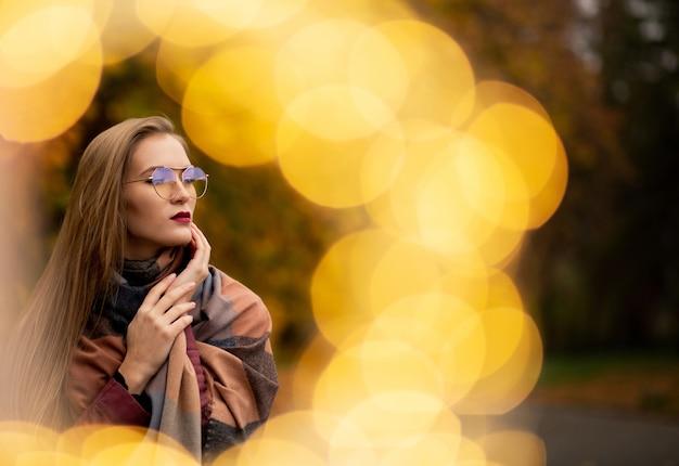 Muito jovem loira brincando com luzes de fada no parque outono. espaço para texto