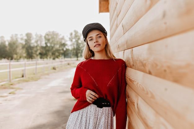 Muito jovem loira de suéter vermelho e chapéu escuro, posando no parque perto da parede de madeira. mulher bonita, vestindo roupas da moda sazonais no outono.