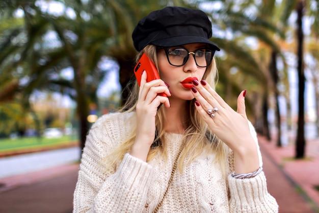 Muito jovem loira fala por seu telefone, roupa casual inteligente, chapéu, suéter e óculos transparentes, emoções positivas, palmeiras ao redor.