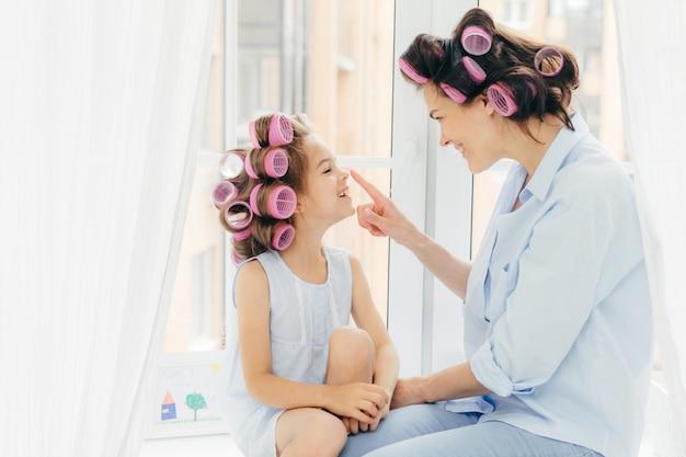 Muito jovem mãe e filha com rolinhos no cabelo, estar de bom humor, aproveitar o tempo em casa