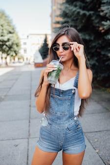 Muito jovem modelo mulher com óculos de sol e camisa na cidade