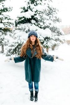 Muito jovem morena de cabelos longos, posando no parque de inverno nevado