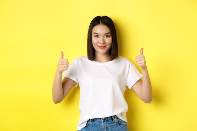 Muito jovem mulher asiática em t-shirt branca, mostrando os polegares para cima e sorrindo, elogie a boa oferta, recomende o produto, satisfeita em pé sobre o fundo amarelo.