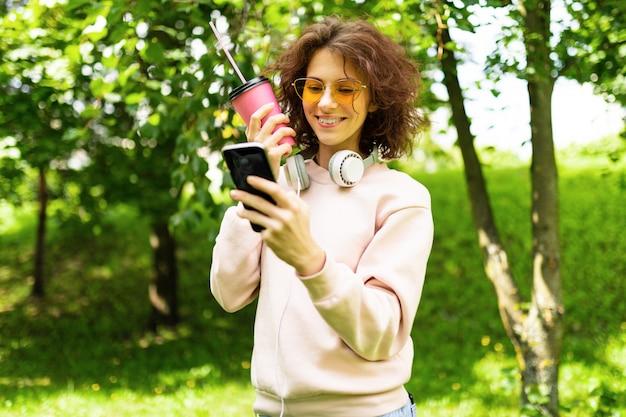 Muito jovem mulher caucasiana dar um passeio no parque com café e fones de ouvido