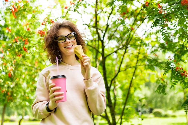 Muito jovem mulher caucasiana dar um passeio no parque com café e sorvete