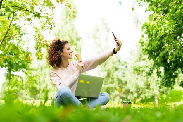 Muito jovem mulher caucasiana está envolvida em freelance no parque com laptop, a xícara de café e sorvete, senta-se em uma grama e faz selfie