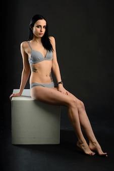 Muito jovem mulher com tatuagem em estúdio, linda e sedutora.