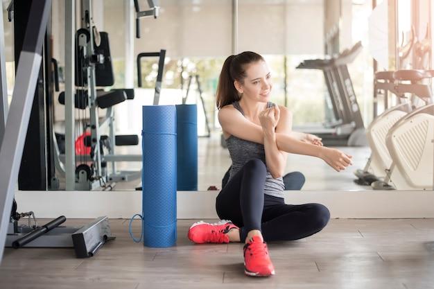Muito jovem mulher desportiva é aquecer no ginásio, estilo de vida saudável
