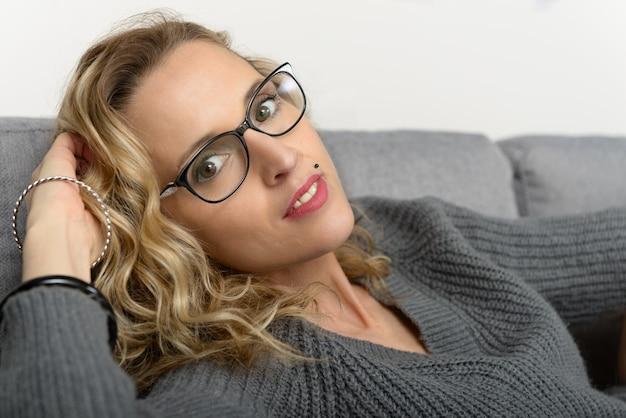 Muito jovem mulher loira com óculos relaxantes