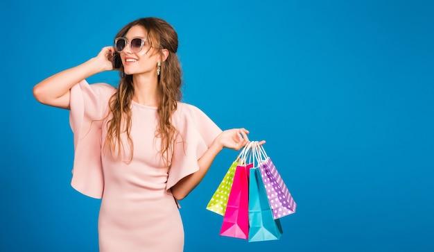 Muito jovem mulher sexy elegante em um vestido de luxo rosa, tendência da moda de verão, estilo chique, óculos de sol, fundo azul studio, compras, segurando sacolas de papel, falando no celular, shopaholic