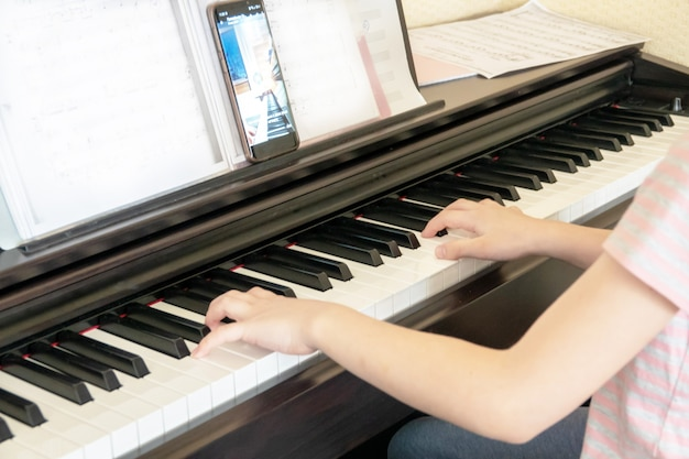 Muito jovem músico tocando piano digital clássico em casa durante a aula on-line em casa, distância social durante a quarentena, auto-isolamento, conceito de educação on-line