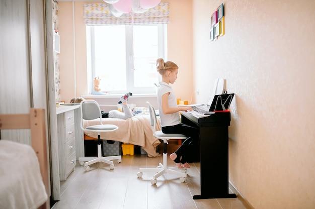 Muito jovem músico tocando piano digital clássico em casa durante as aulas online em casa.