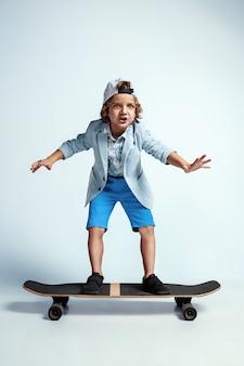 Muito jovem no skate em roupas casuais na parede branca. andando e parece feliz. pré-escolar do sexo masculino, caucasiano, com emoções faciais brilhantes. infância, expressão, diversão.