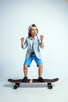 Muito jovem num skate com roupas casuais na parede branca do estúdio