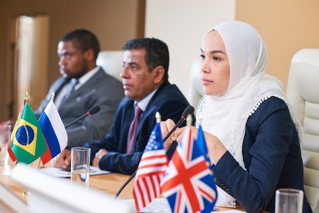 Muito jovem, participante de hijab e roupa formal, ouvindo o discurso de um colega estrangeiro na convenção internacional