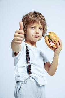 Muito jovem rapaz encaracolado com roupas casuais na parede branca do estúdio. comendo hambúrguer