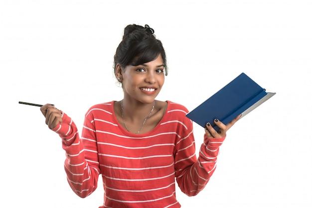 Muito jovem, segurando o livro e posando no espaço em branco