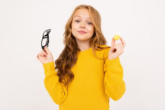 Muito jovem, segurando um recipiente para lentes e óculos na mão