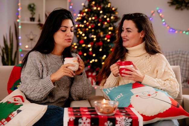 Muito jovem sorridente segura a xícara e olha para a amiga satisfeita segurando a xícara sentada nas poltronas com os olhos fechados e aproveitando o natal em casa