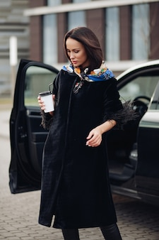 Muito jovem vestindo um casaco preto elegante, mantendo o café e em pé perto do carro. conceito de cidade da moda