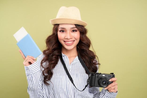 Muito jovem viajante com uma câmera digital apoiada em sua mala e sorrindo para a câmera