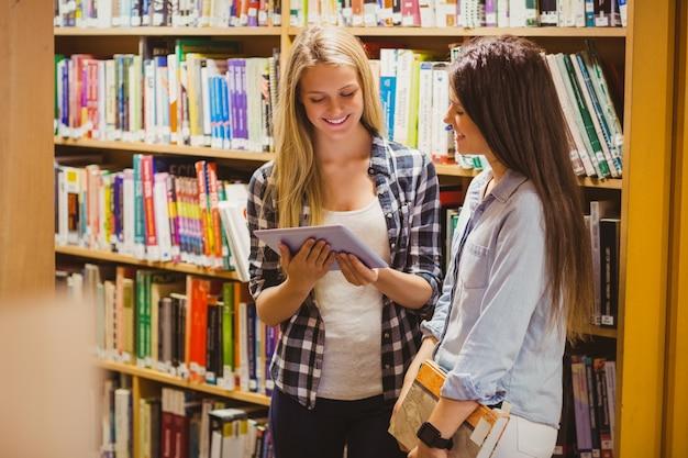 Muito jovens estudantes trabalhando em conjunto com o tablet na biblioteca