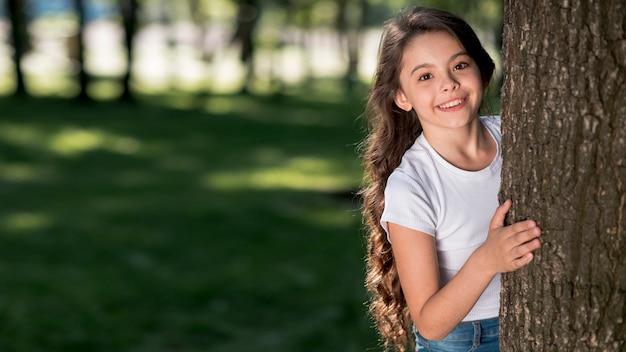 Muito linda garota a espreitar do tronco de árvore no parque