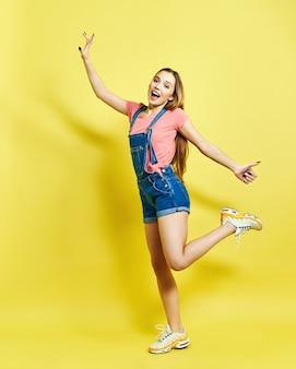 Muito linda garota feliz e animada está pulando, com roupa de verão, em fundo amarelo