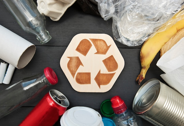 Muito lixo diferente na mesa e o ícone de reciclagem entre eles