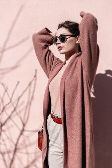 Muito na moda mulher jovem e bonita com lábios sensuais em elegantes óculos de sol, posando de pé no sol perto de parede rosa vintage na cidade. menina elegante com roupa elegante endireita o cabelo luxuoso. estilo retrô