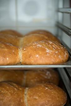 Muito pão fresco ready-made em um forno da padaria em uma padaria.