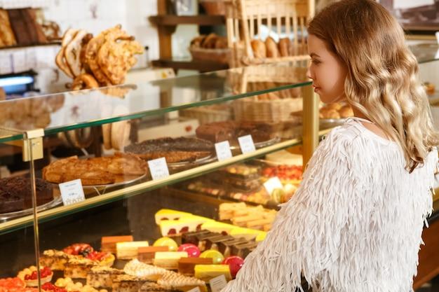 Muito para escolher. mulher loira linda olhando para vitrine de padaria e escolhendo sobremesa para comprar