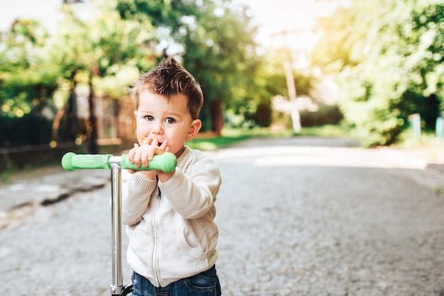 Muito pequeno garoto andando de scooter ao ar livre na rua