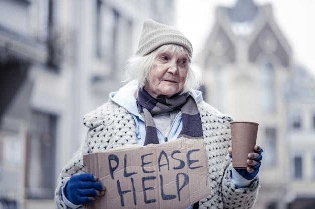 Muito pobre. mulher idosa sem-teto segurando um copo de papel enquanto pede dinheiro às pessoas