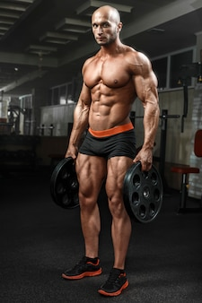 Muito poder cara atlético em pé no ginásio e lokking na câmera