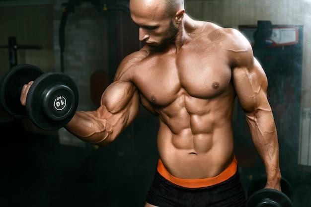 Muito poderoso cara atlético trabalhando no ginásio com halteres
