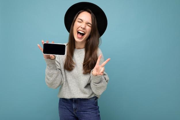 Muito positiva jovem mulher usando chapéu preto e suéter cinza segurando o telefone, mostrando o smartphone isolado no fundo, mostrando um gesto de paz.